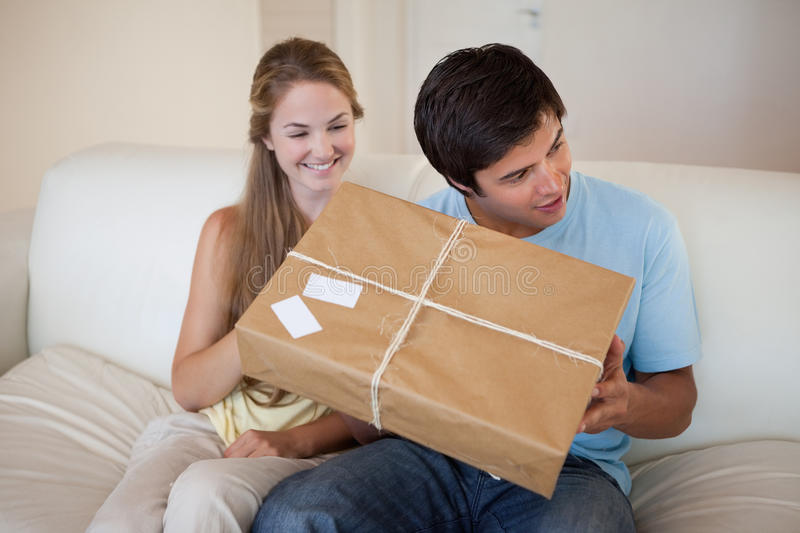 Smiling couple opening a package. In their living room royalty free stock photography