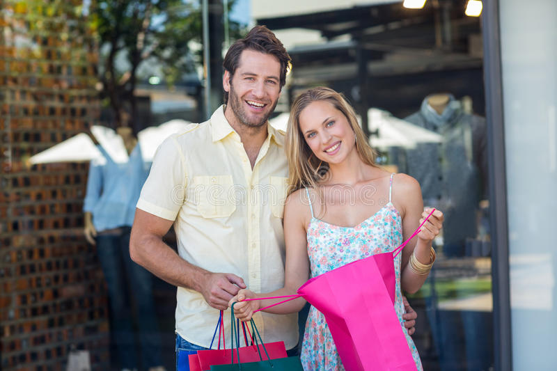 Smiling couple opening shopping bag stock images