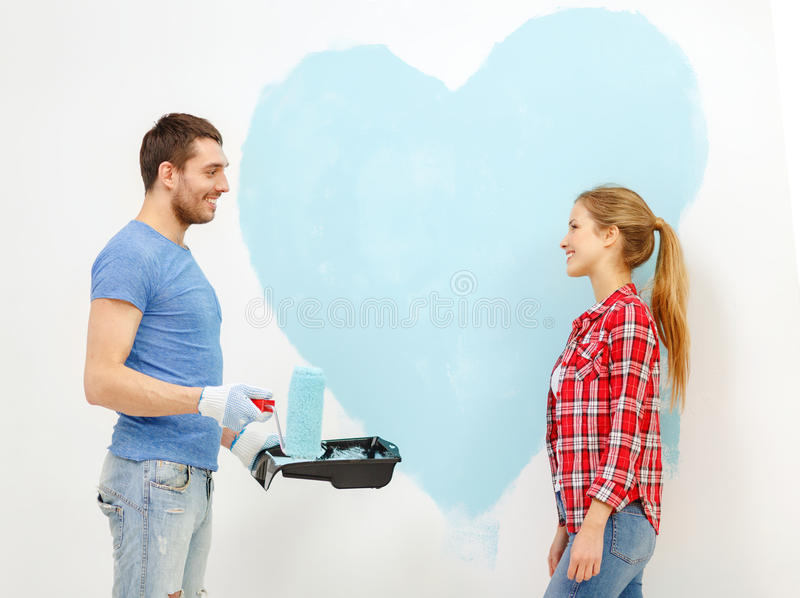 Smiling couple painting big heart on wall royalty free stock photography