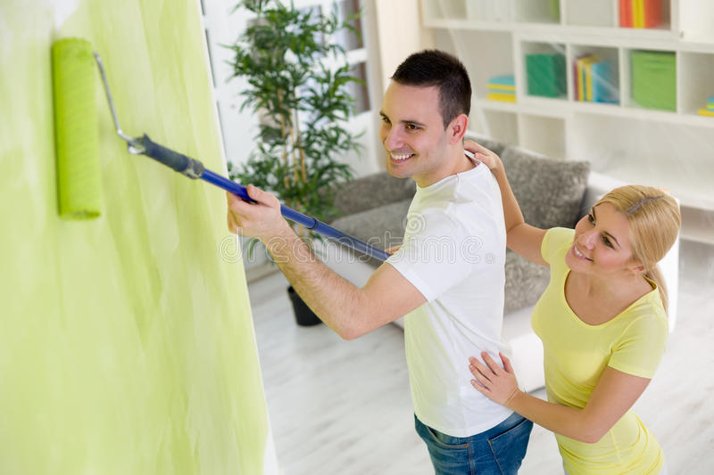 Smiling couple painting hew home. Smiling young couple painting their hew home royalty free stock photo