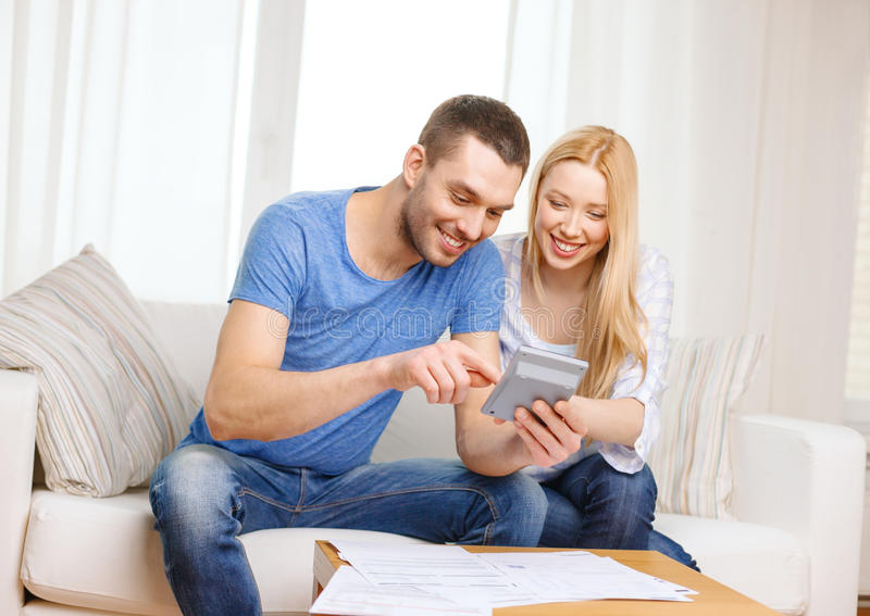 Smiling couple with papers and calculator at home. Tax, finances, family, home and happiness concept - smiling couple with papers and calculator at home royalty free stock photos