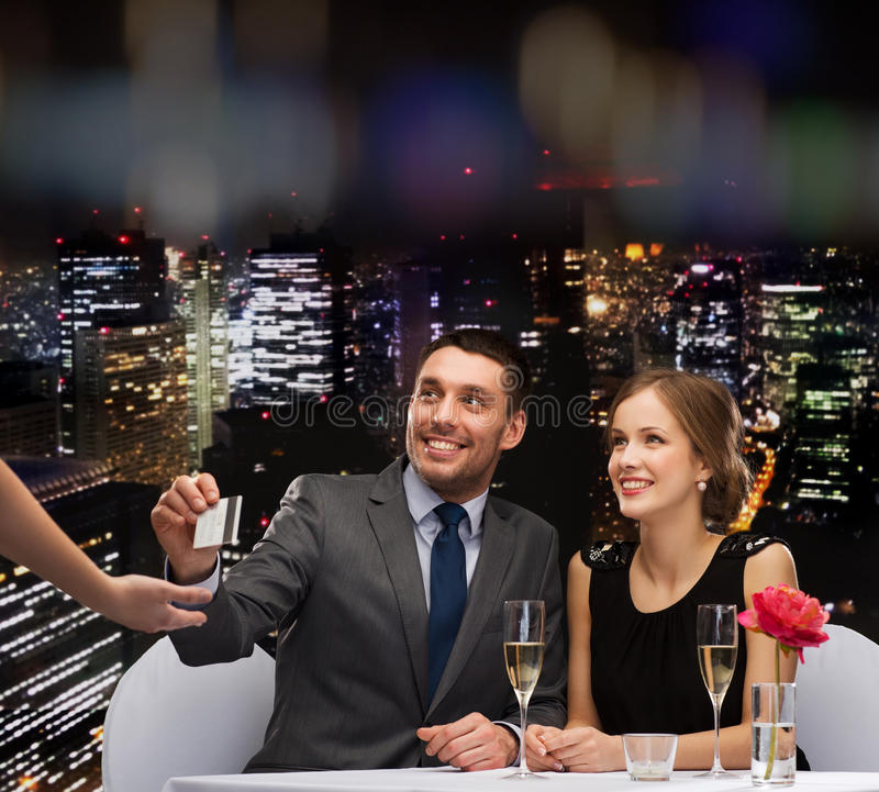 Smiling couple paying for dinner with credit card. Restaurant, couple and holiday concept - smiling couple paying for dinner with credit card at restaurant stock image