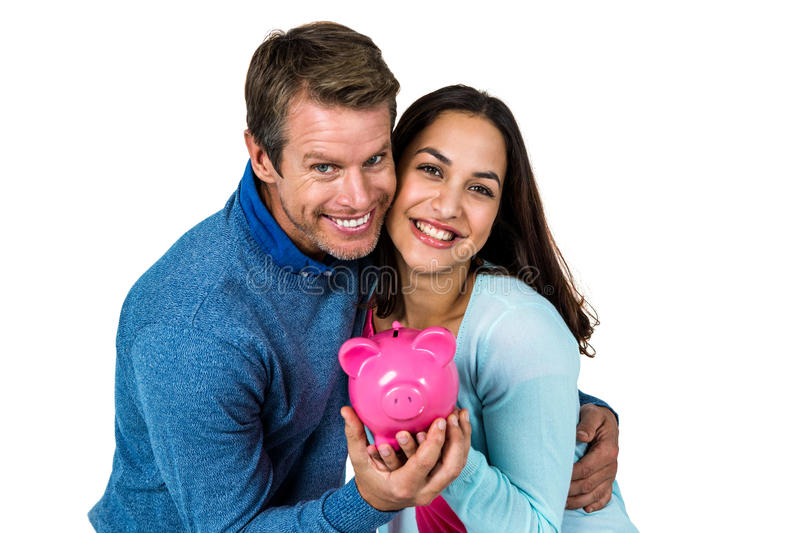 Smiling couple with pink piggy bank stock images