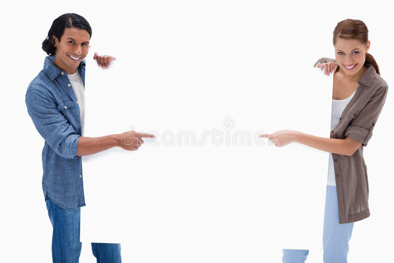 Smiling couple pointing at blank sign in their hands royalty free stock photography