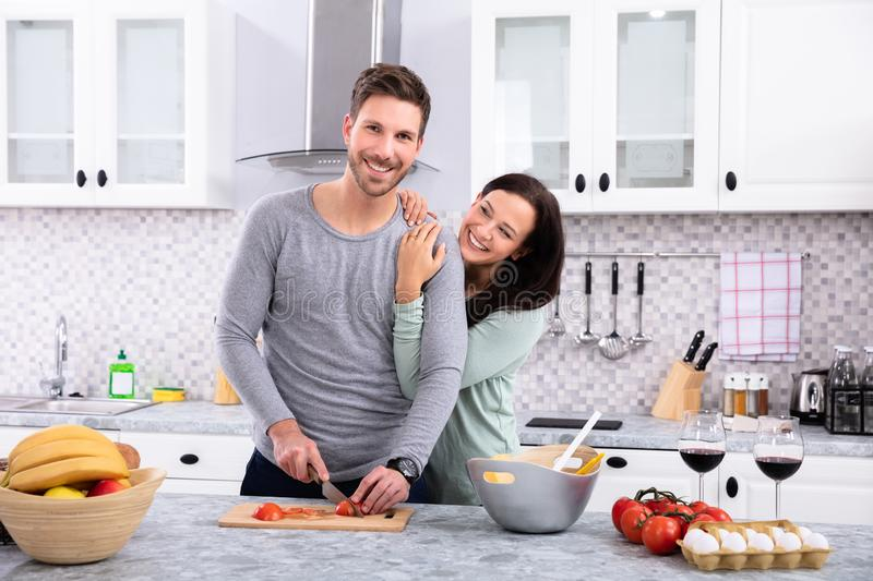 Smiling Couple Preparing Food In Kitchen. Front View Of Man With His Wife Cutting Vegetable On Chopping Board At Kitchen Worktop royalty free stock photo
