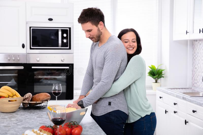Smiling Couple Preparing Food In Kitchen. Side View Of Man With His Wife Cutting Vegetable On Chopping Board At Kitchen Worktop stock image