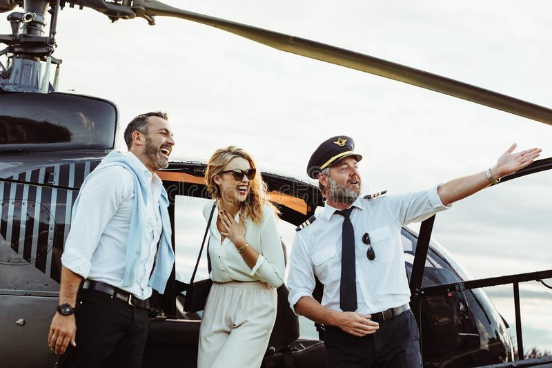 Smiling couple by a private helicopter with pilot royalty free stock image