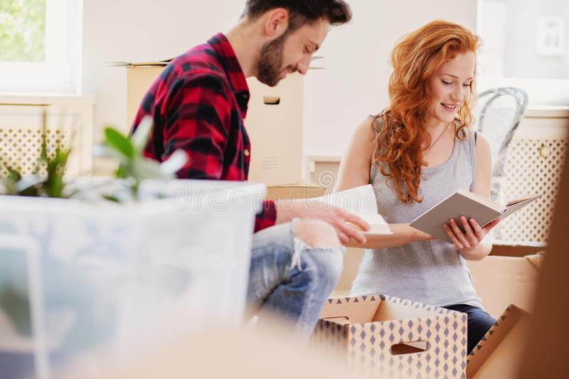 Smiling couple reading books while unpacking stuff after relocation to new flat royalty free stock images