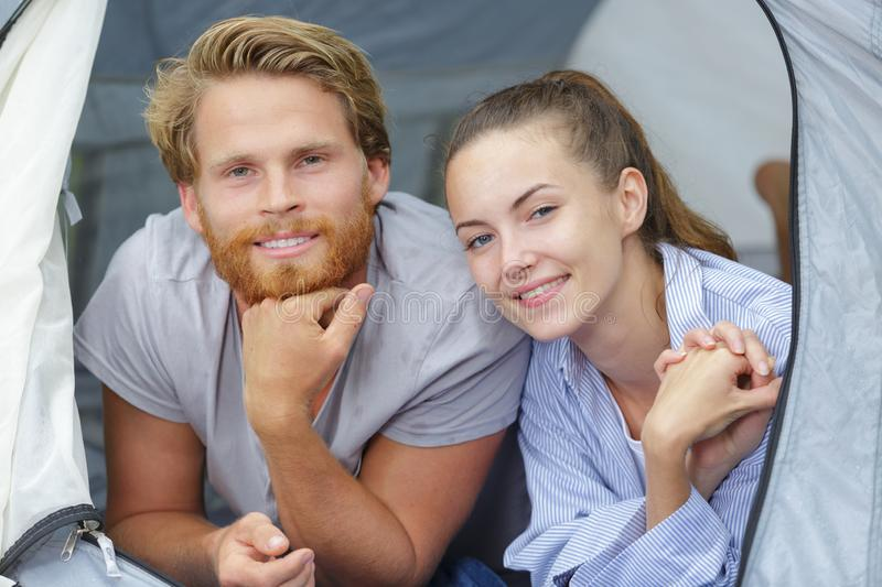 Smiling couple resting in camping tent stock photos