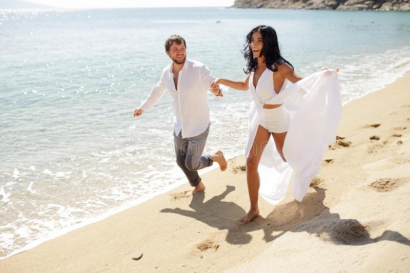 Smiling couple run on beach, in wedding clothing, enjoying in honeymoon, in summer time, sunny day, holiday, Greece. Happy couple run on white beach, wear in stock photo