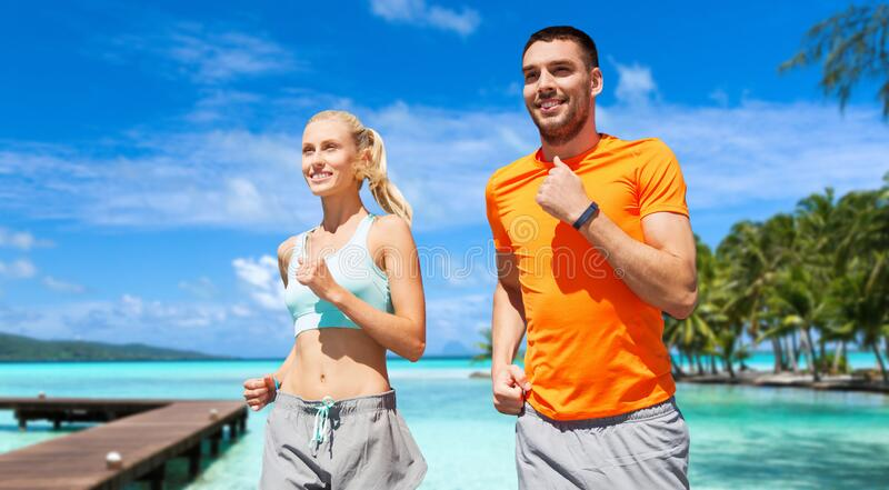 Smiling couple running along exotic on beach stock image
