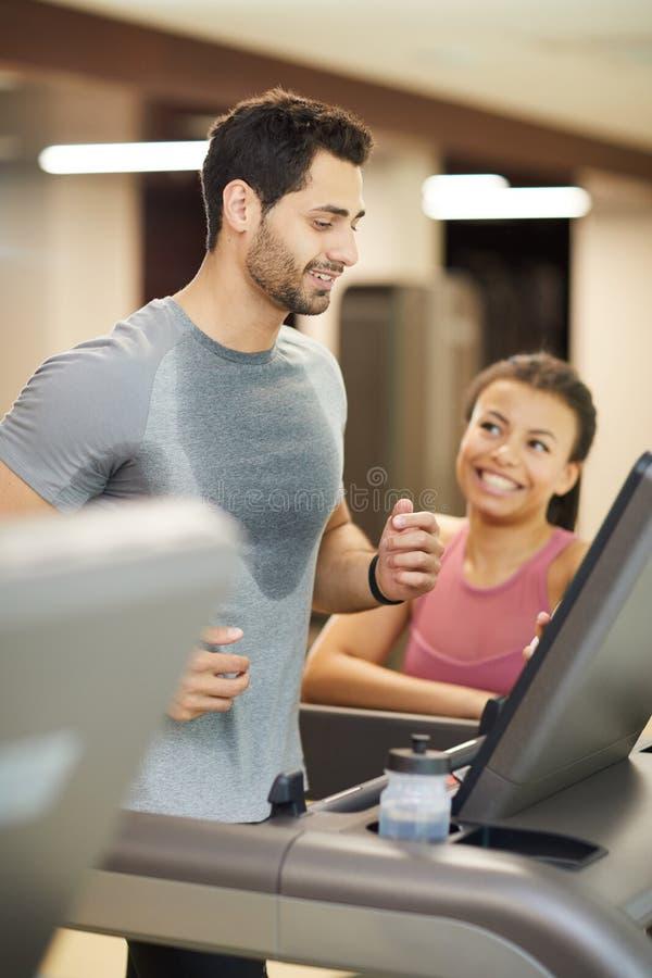 Smiling Couple Running on Treadmill stock image