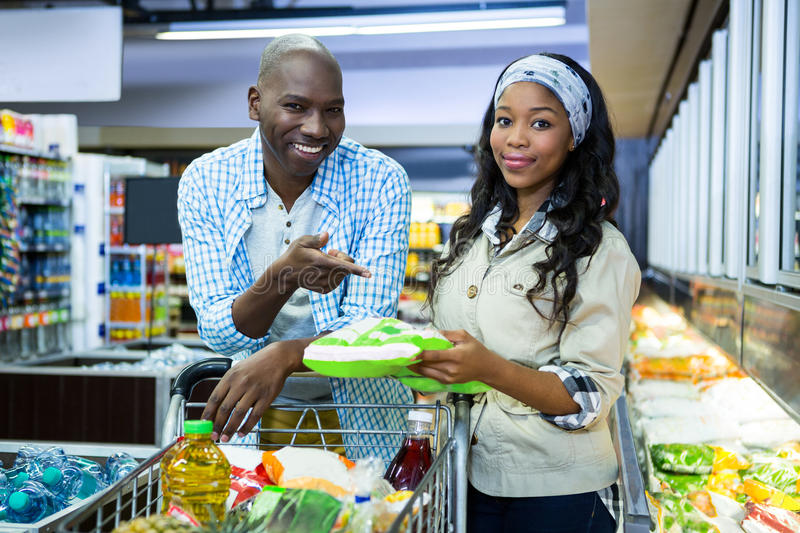 Smiling couple shopping in grocery section at supermarket. Portrait of smiling couple shopping in grocery section at supermarket royalty free stock photo