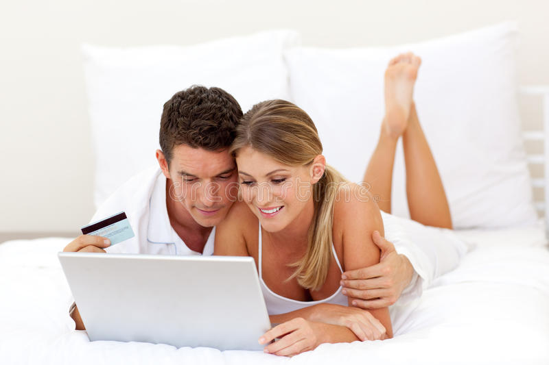 Smiling couple shopping online. Lying on their bed stock image