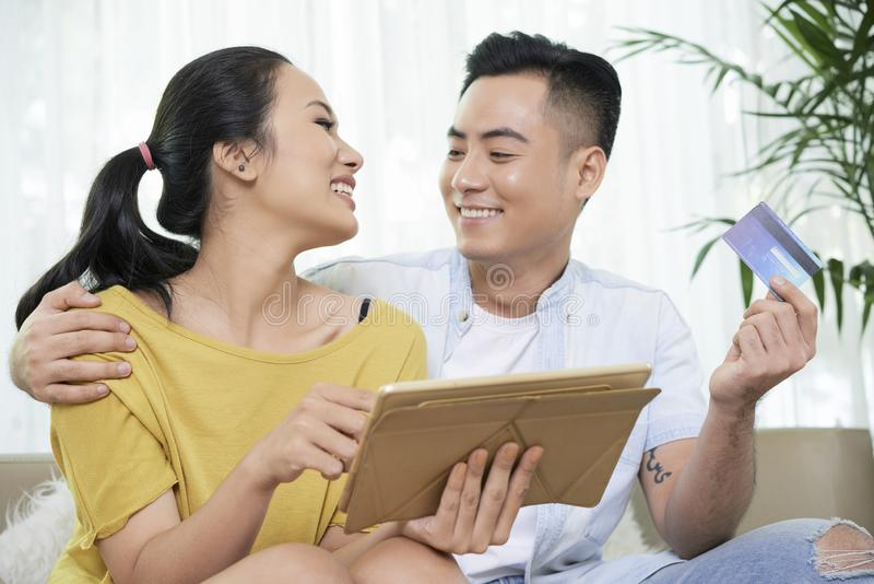 Smiling couple shopping online with tablet. Loving Asian men and women with tablet and credit card smiling while shopping online at home stock photos