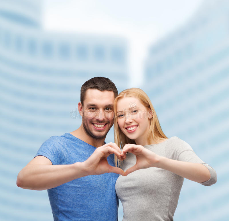 Smiling Couple Showing Heart With Hands Stock Photo