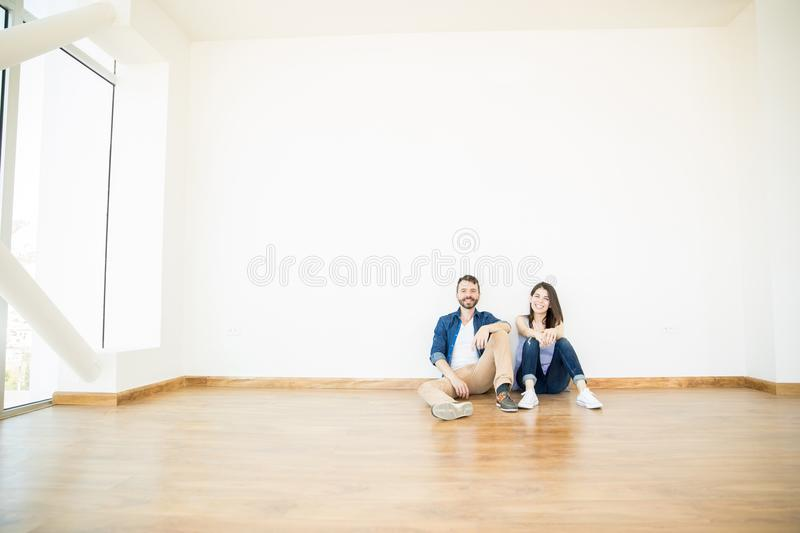Smiling Couple Sitting In Empty Room Of New Apartment royalty free stock photos
