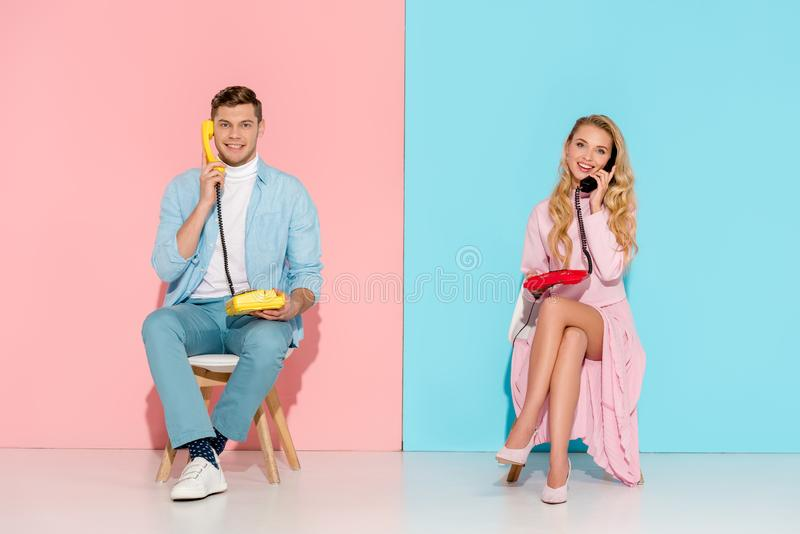 Smiling couple sitting and having conversation on vintage telephones. With pink and blue background royalty free stock images