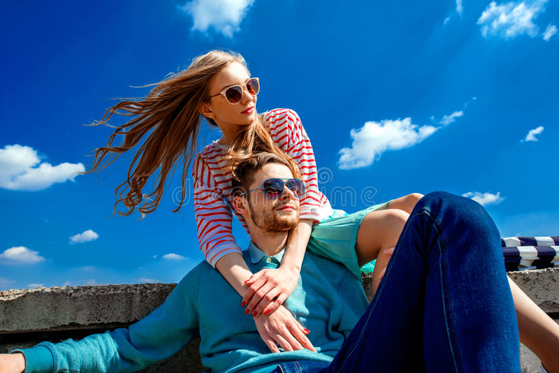 Smiling couple sitting on the roof embracing and smiling on the. Blue sky background royalty free stock photography