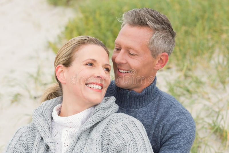 Smiling couple sitting on the sand stock image