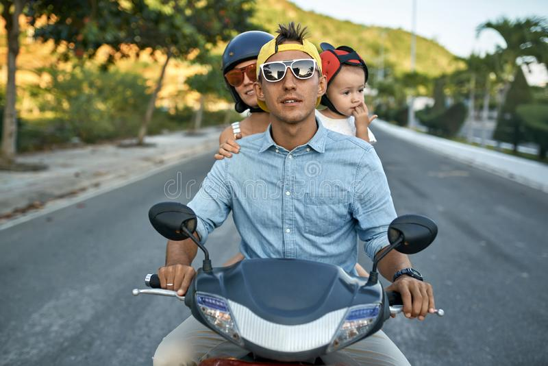 Parents with their little kid riding motorcycle on sunny city street royalty free stock image