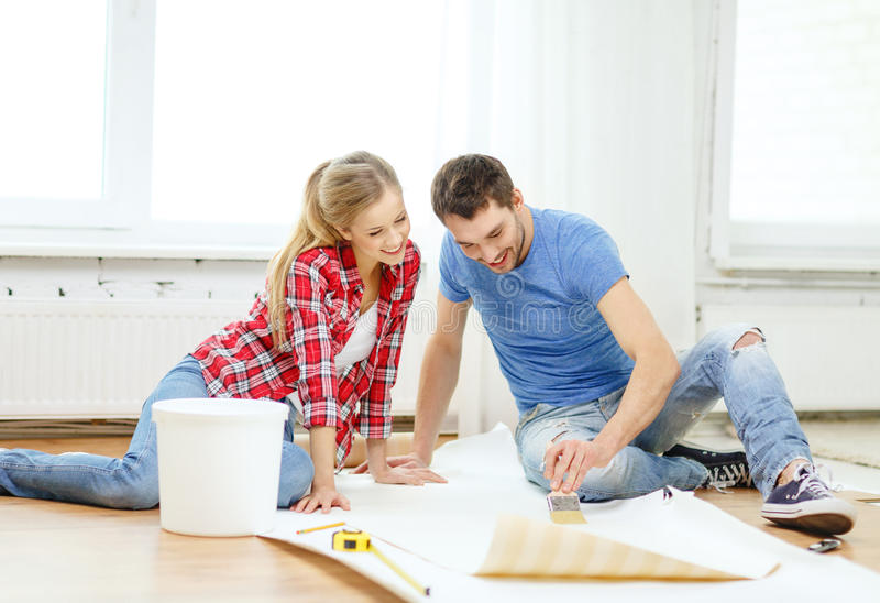 Smiling couple smearing wallpaper with glue. Repair, building and home concept - smiling couple smearing wallpaper with glue stock photography