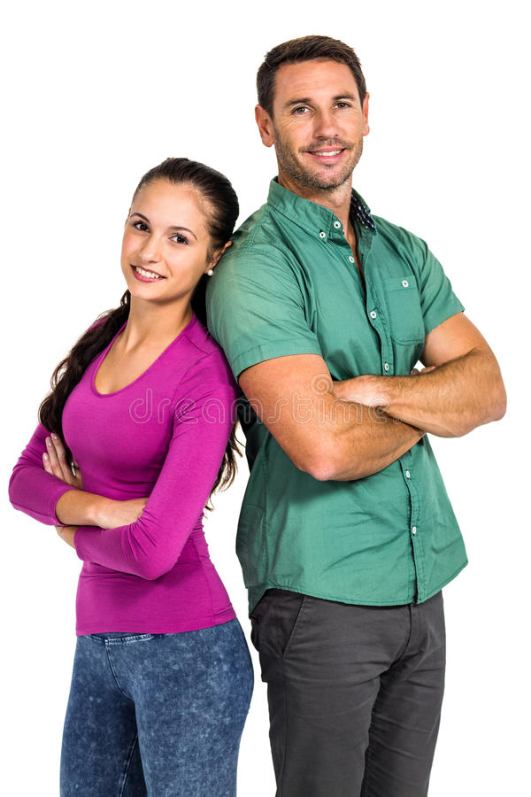Smiling couple standing back to back with arms crossed looking at the camera. On white screen royalty free stock images