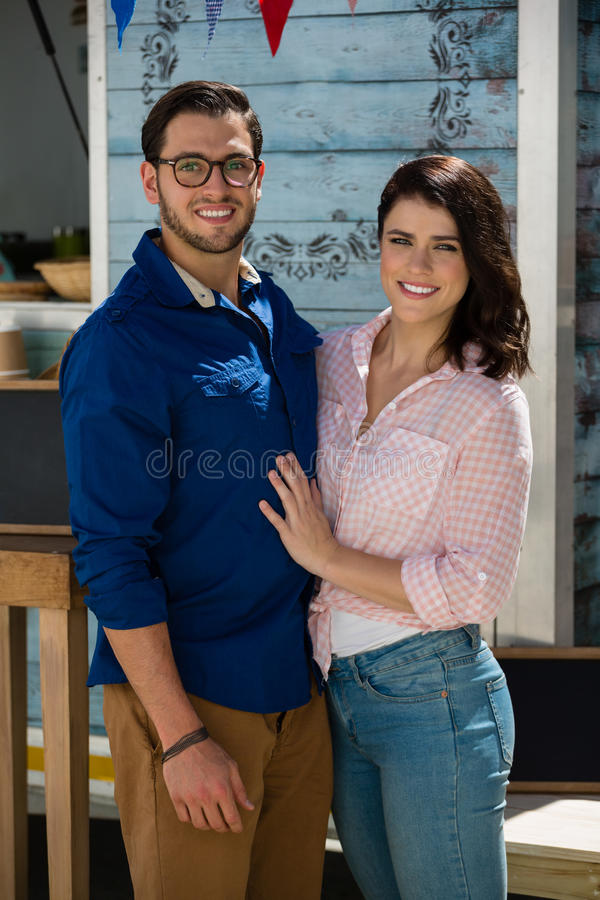 Smiling couple standing by food truck royalty free stock photo