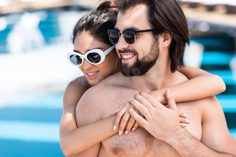 smiling couple in sunglasses embracing royalty free stock photos