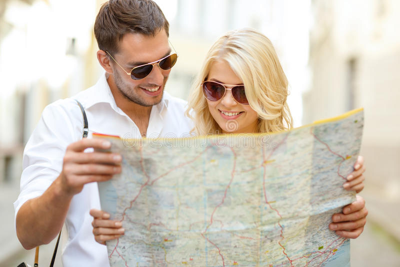 Smiling couple in sunglasses with map in the city royalty free stock photos