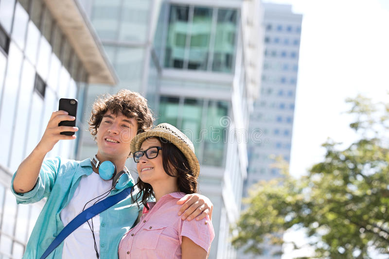 Smiling couple taking self portrait outside office building stock image