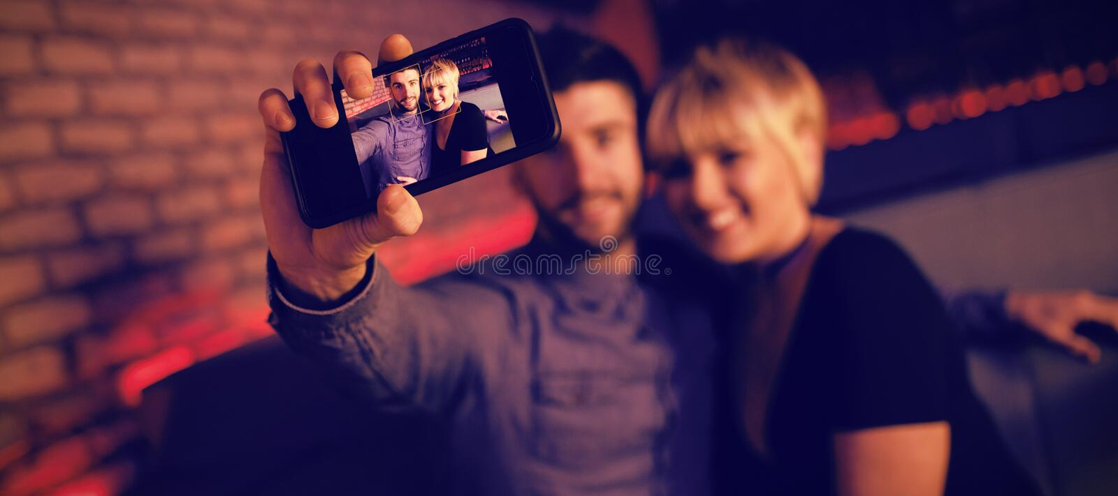 Couple taking selfie on mobile phone in bar royalty free stock images