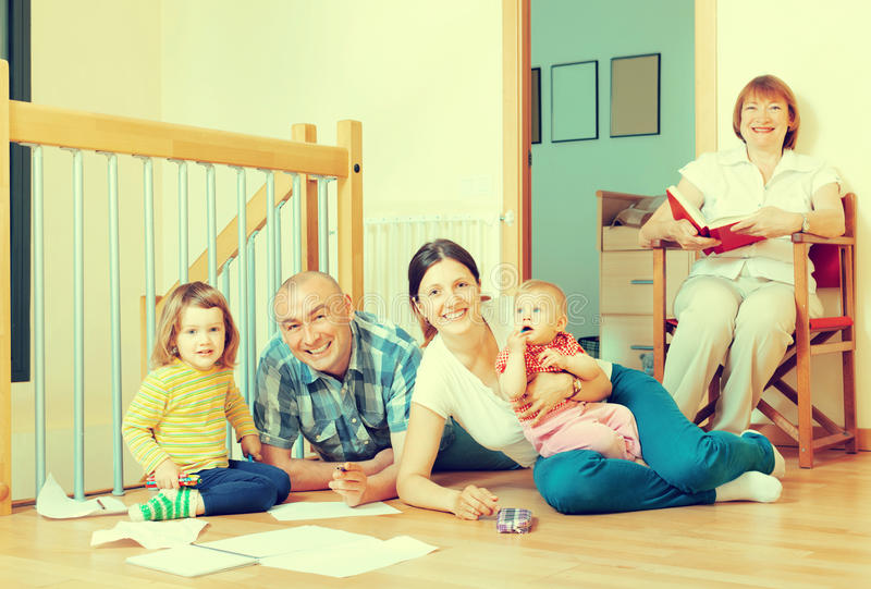 Smiling couple with their offspring and grandmother on floor at. Happy couple with their offspring and grandmother on floor at home royalty free stock photo