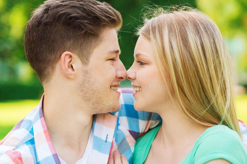 Smiling couple touching noses in park. Holidays, vacation, love and friendship concept - smiling couple touching noses in park stock images