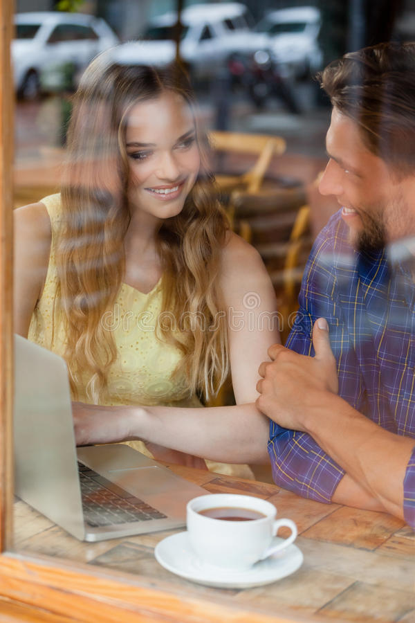 Smiling couple using digital laptop while sitting at cafe stock photos