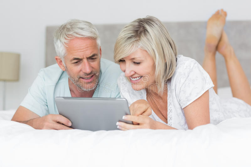 Smiling couple using digital tablet in bed royalty free stock image