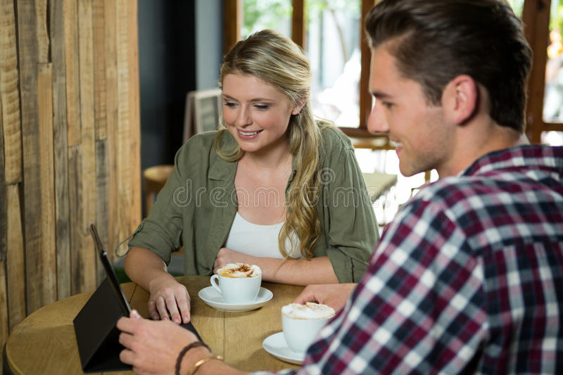 Smiling couple using digital tablet at table in cafe stock photography