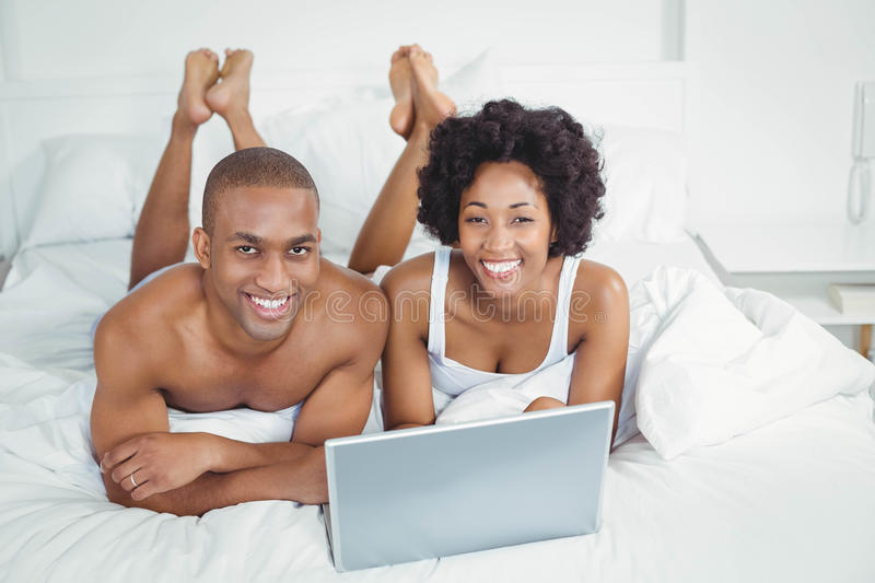 Smiling couple using laptop on bed. At home stock photo