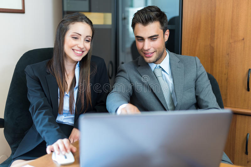 Smiling couple using a laptop computer. Smiling business people using a laptop computer in their office royalty free stock photography
