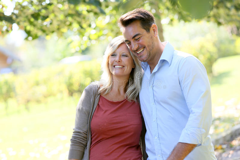 Smiling couple walking in countryside royalty free stock photo