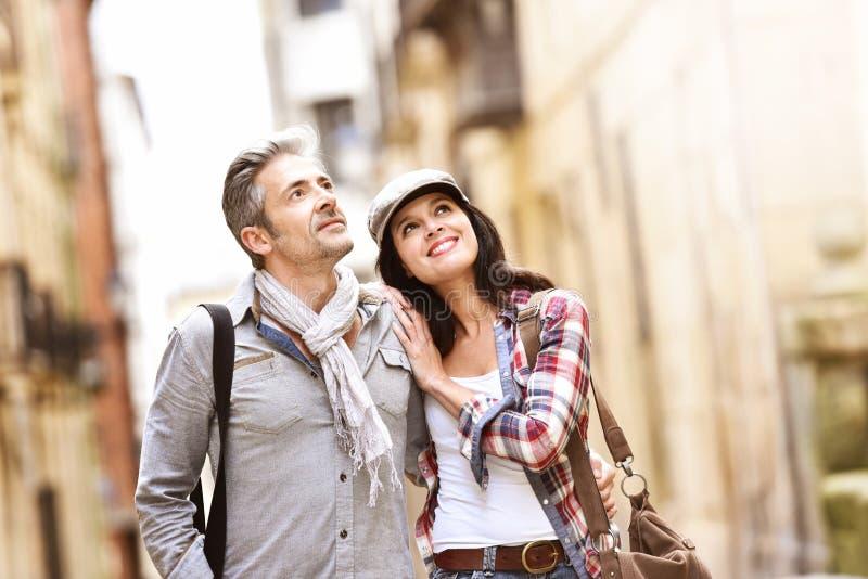 Smiling couple walking in pedestrian street royalty free stock image