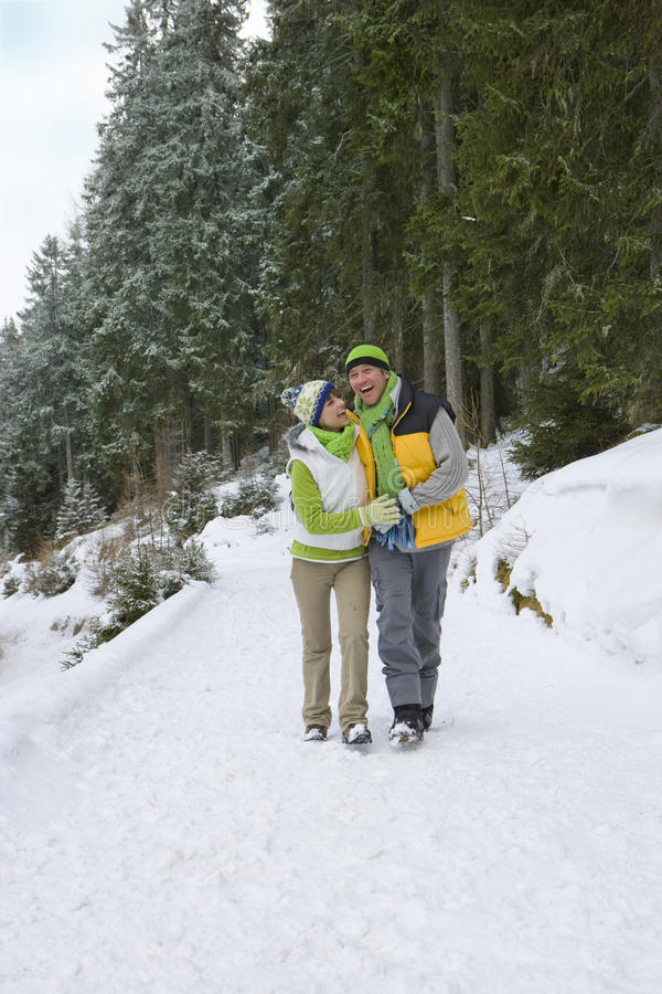Smiling couple walking in snowy woods together stock photos