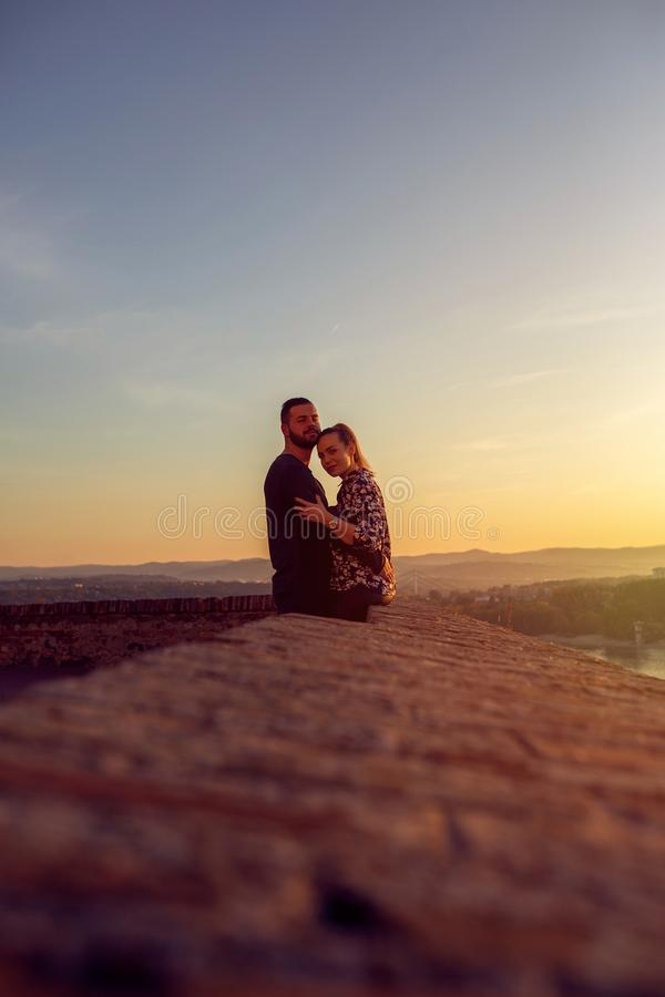 Smiling couple watching the sunset stock photos