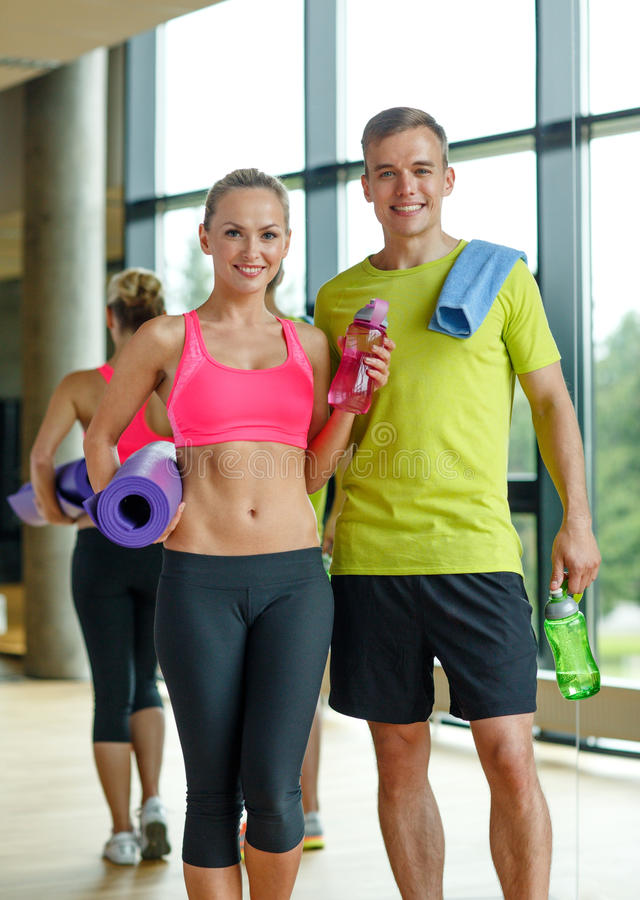 Smiling couple with water bottles in gym stock photos