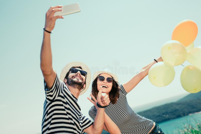 Smiling couple wearing sunglasses with balloons make selfie photo. Over sea background royalty free stock images