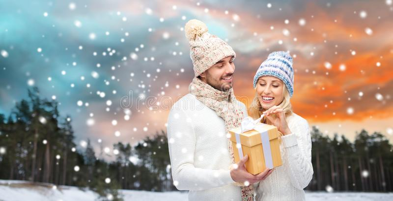 Smiling couple in winter clothes with gift box stock photo