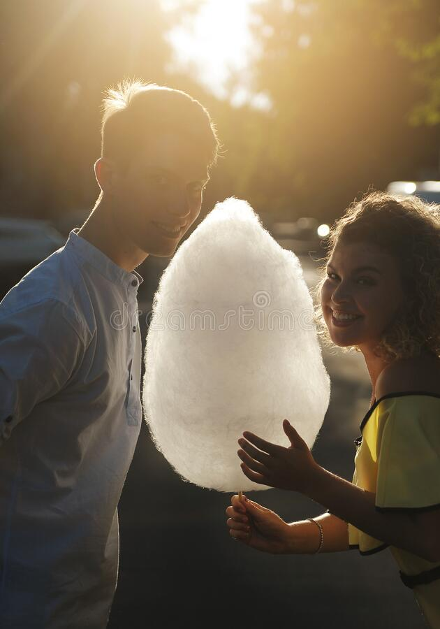 Free Smiling Couple With Cotton Candy Walking Outdoors Stock Images - 189477724
