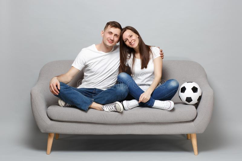 Smiling couple woman man football fans in white t-shirt cheer up support favorite team with soccer ball, hugging royalty free stock images