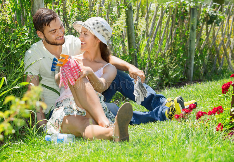 Smiling couple working in garden. Smiling happy couple working in the flower garden stock photos