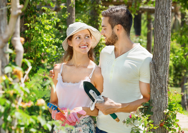 Smiling couple working in garden. Smiling happy couple working in the flower garden stock photo
